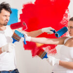 Young funny couple are doing repair at home and painting a wall with roller.